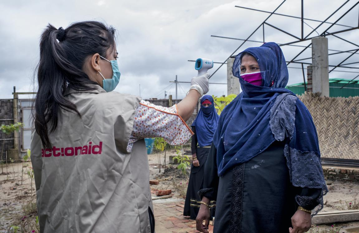 ActionAid worker Uthiya yea Marma is checking Anowara's body temperature before letting her enter inside ActionAid's women-friendly space.