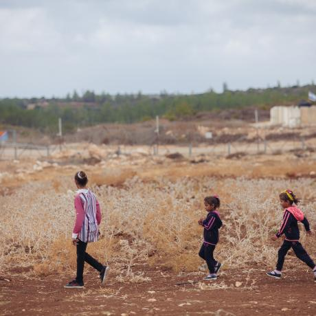 Ameera, 11, and her sisters walk along their farmland in the West Bank