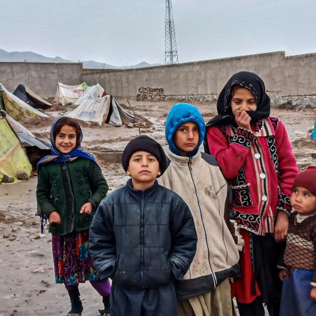 Children stand in front of tents in a camp for internally displaced people in Afghanistan