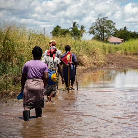 Women walk through flooded fields in Buzi, Mozambique