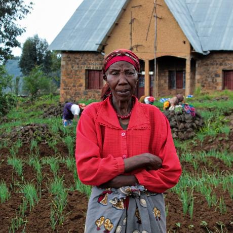 Asteria stands in front of her crops, Rwanda.
