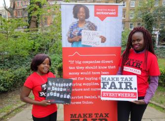 Two women holding posters calling for fair taxation