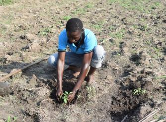Okech practices his farming skills in Uganda