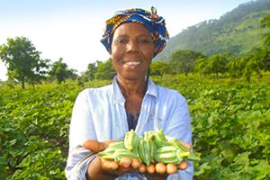 A woman farmer holding some produce from her farm